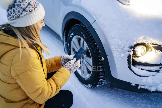 Доросла жінка користується мобільним телефоном, прилягаючи на засніженій машині. — стокове фото