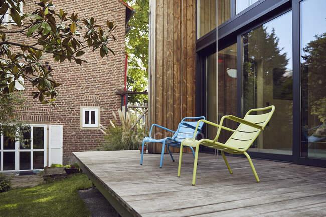 Пусті стільці на дерев'яній підлозі біля крихітного будинку. — стокове фото