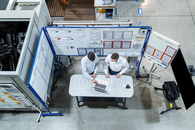 Professionnels masculins utilisant un ordinateur portable au bureau tout en planifiant dans l'industrie — Photo de stock