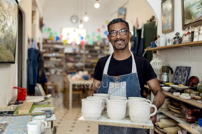 Усміхаючись самець тримає кераміку, стоячи в майстерні. — стокове фото