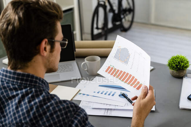 Architect analyzing graph while sitting by desk at office — Stock Photo