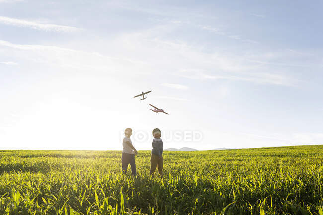Boys looking at flying airplane toy while standing on grass in meadow — стокове фото
