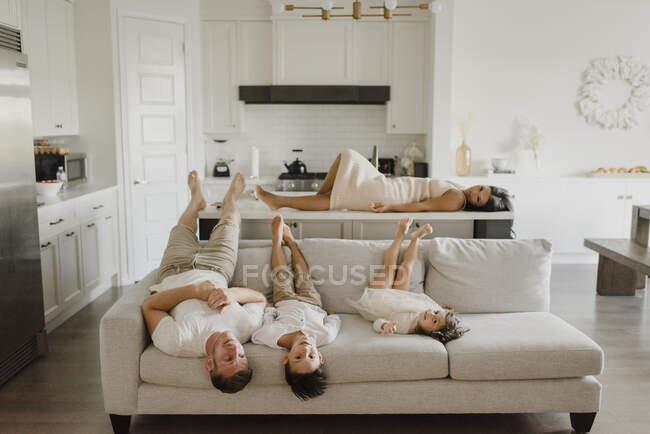 Отец лежит с детьми на диване, в то время как мать отдыхает по кухне острова дома — стоковое фото