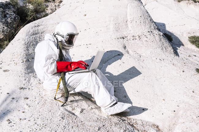 Astronauta masculino trabalhando sobre laptop enquanto sentado na montanha — Fotografia de Stock