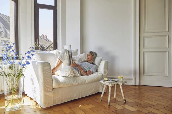 Жінка читає журнал на дивані у вітальні. — стокове фото