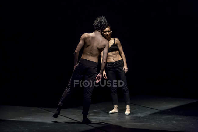 Male and femal dancer performing contemporary ballet on black stage — Stock Photo