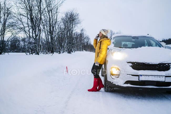 Доросла жінка розмовляє по мобільному телефону, стоячи на сніговому ландшафті. — стокове фото