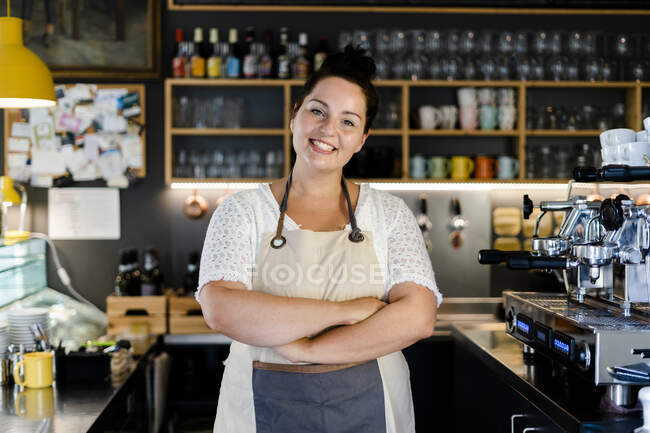 Посмішка бариста зі схрещеними руками стоїть у кав
