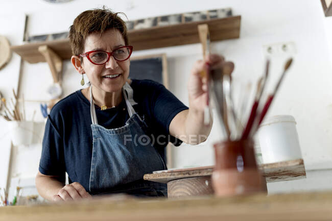 Artista sorridente escolhendo pincel na oficina de cerâmica — Fotografia de Stock
