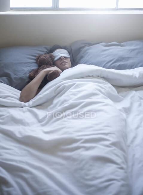 Jovem mulher usando máscara ocular dormindo com brinquedo na cama em casa — Fotografia de Stock