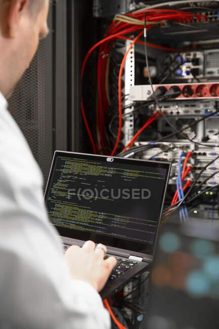 Закриття чоловічого ІТ-професіонала за допомогою ноутбука в центрі обробки даних. — стокове фото