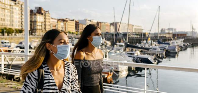 Mujeres jóvenes con mascarilla protectora en la ciudad - foto de stock