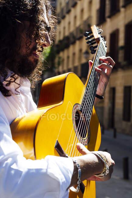 Guitarrista tocando la guitarra de pie en la calle de la ciudad - foto de stock