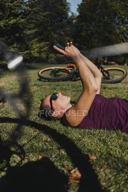 Sportswoman using mobile phone while resting on grass by electric mountain bike at park — Stock Photo