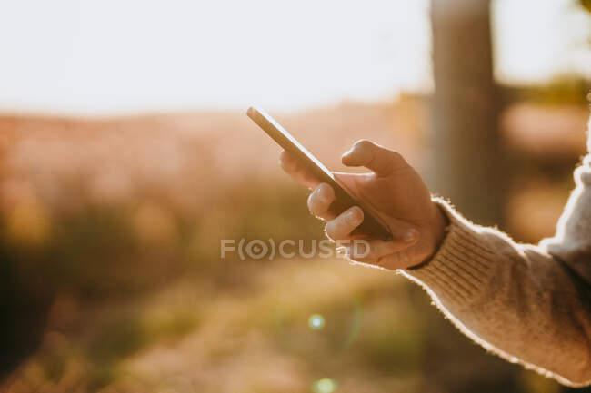 Mão de homem usando telefone celular enquanto está na floresta — Fotografia de Stock