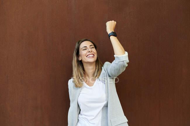 Mujer de negocios alegre con la mano levantada de pie contra la pared marrón - foto de stock
