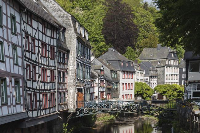 Alemania, Renania del Norte-Westfalia, Monschau, Casas de entramado de madera a lo largo del canal del río Rur - foto de stock