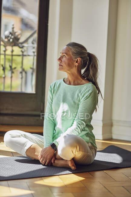 Задумчивая женщина смотрит вдаль на коврик для упражнений на полу в гостиной — стоковое фото