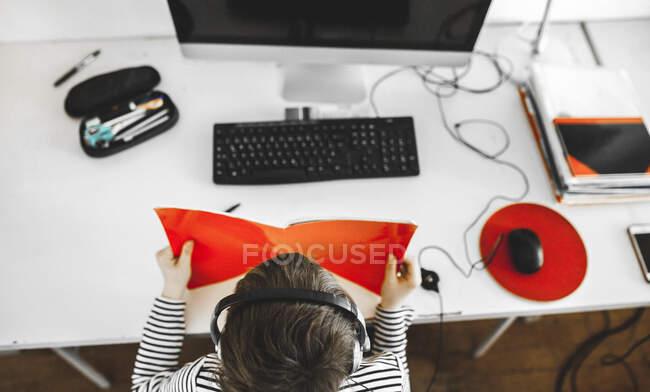 Хлопчик показує свої домашні шкільні результати веб-камерам на комп'ютері, відеоконференції, зверху — стокове фото