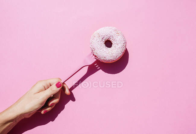 Mano de mujer sosteniendo tenedor con rosquilla dulce - foto de stock