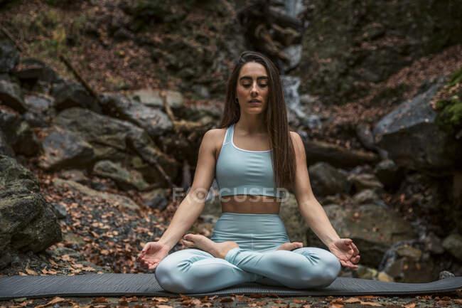 Спортивная женщина медитирует, сидя со скрещенными ногами у водопада в лесу — стоковое фото
