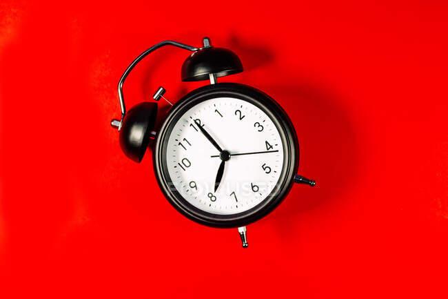 Reloj despertador contra fondo rojo - foto de stock