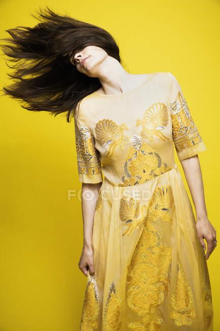 Mulher madura jogando cabelo enquanto está de pé contra o fundo amarelo — Fotografia de Stock