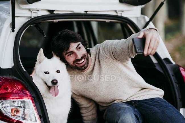 Усміхнений чоловік бере сельфі з собакою, сидячи в багажнику автомобіля в лісі. — стокове фото