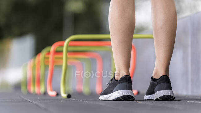 Legs of young woman standing by small hurdle — Stock Photo