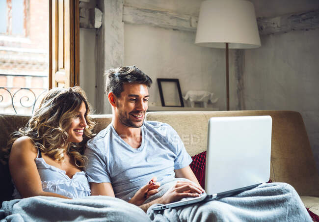 Happy young couple sitting on couch at home watching laptop — Stock Photo