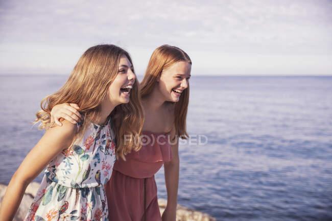 Amigos rindo de pé na calçada durante o dia ensolarado — Fotografia de Stock