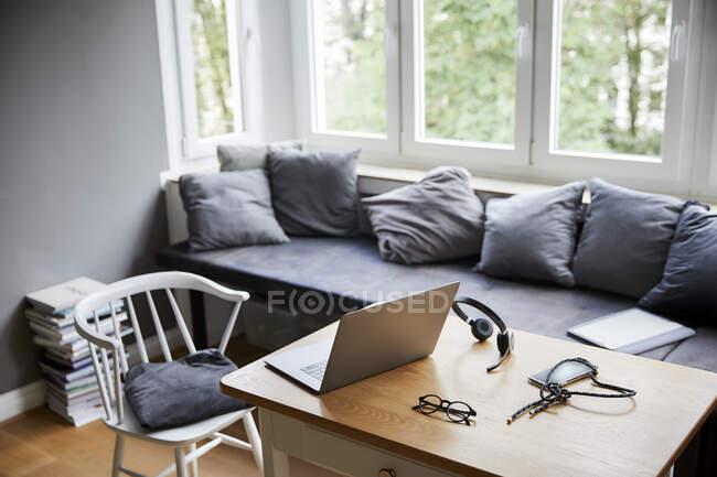 Ноутбук на столі меблями у вітальні. — стокове фото