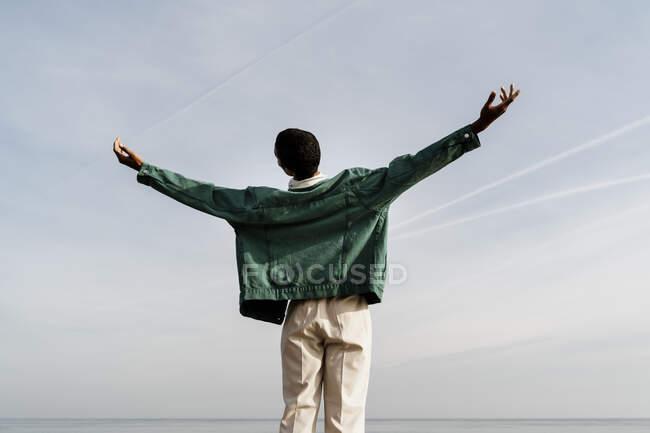 Joven con los brazos extendidos contra el cielo - foto de stock