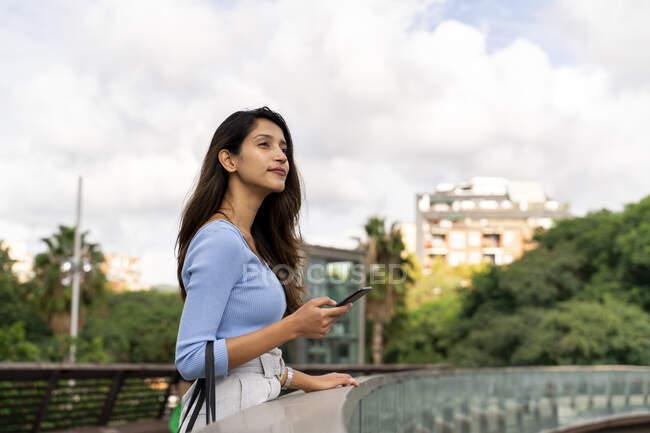 Pensativa mujer de negocios sosteniendo el teléfono móvil mientras está de pie en la pasarela - foto de stock