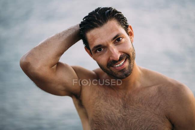 Чоловік без сорочки з волоссям, що посміхається проти моря. — стокове фото