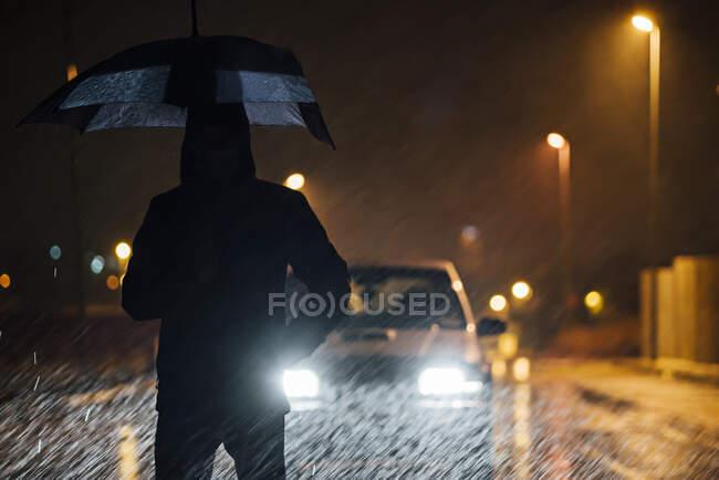 Молодий чоловік з парасолькою стоїть перед автомобільним дутингінгом дощової ночі. — стокове фото