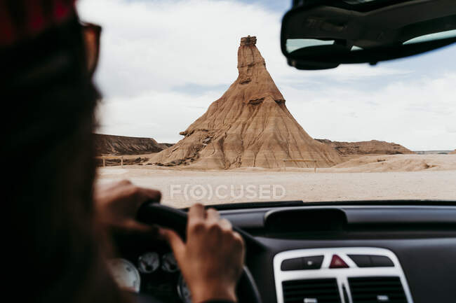 Spain, Navarre, Young woman driving car towards sandstone rock formation in Bardenas Reales — стоковое фото