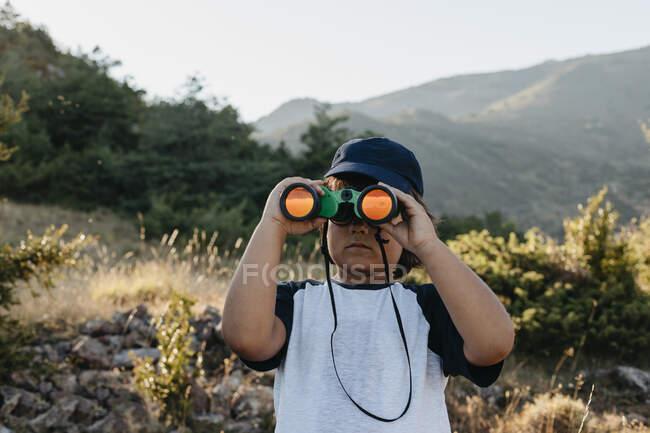 Boy using binocular while standing on mountain — Stock Photo
