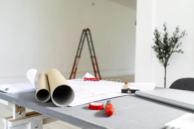 Rolled up blueprints lying on desk in architect studio — Stock Photo