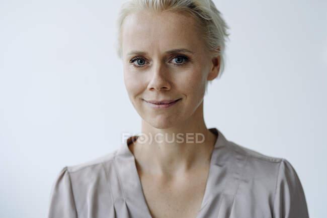 Nahaufnahme einer selbstbewussten Geschäftsfrau vor weißer Wand im Büro — Stockfoto
