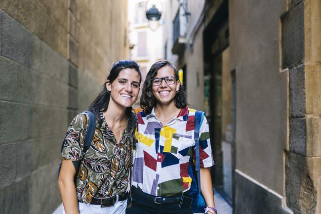 Heureux couple lesbien souriant tout en se tenant sur l'allée au milieu de l'immeuble en ville — Photo de stock