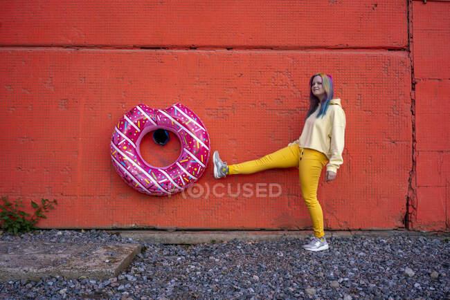 Молода жінка з пофарбованим волоссям і плаваючою шиною, що звисає на червоній стіні. — стокове фото