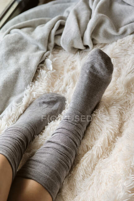 Woman wearing socks relaxing on fur at home — Stock Photo
