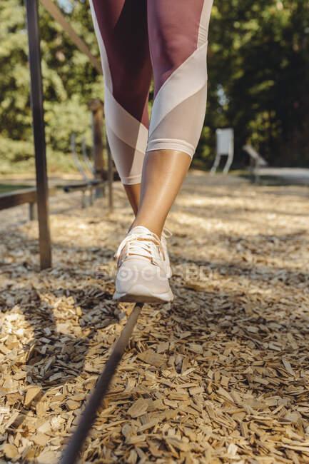 Крупный план женщины, балансирующей на веревке на фитнес-тропе — стоковое фото