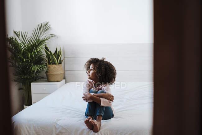 Презрение к девушке, сидящей на кровати в спальне дома — стоковое фото