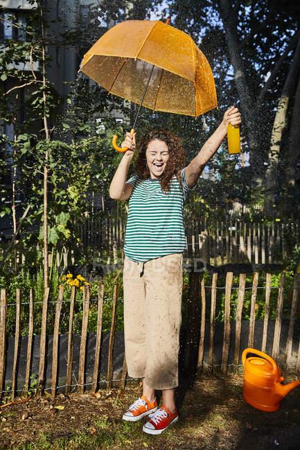 Весела жінка з ротом, що тримає пляшку і парасольку, стоячи на подвір