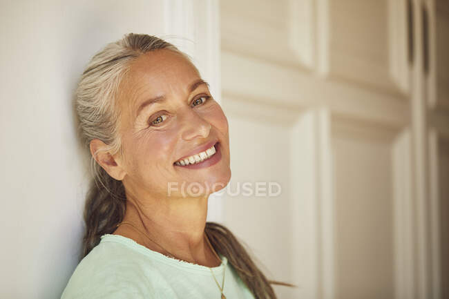 Wrinkled woman against wall at home — Stock Photo