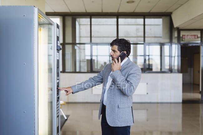 Професор, який розмовляє по телефону, користуючись торгівельною машиною в кафетерії в університеті. — стокове фото