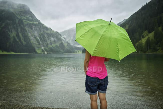 Mulher madura de pé com guarda-chuva verde em Vilsalpsee lago durante a estação chuvosa — Fotografia de Stock
