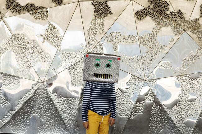 Boy wearing robot mask standing against silver patterned wall — Foto stock